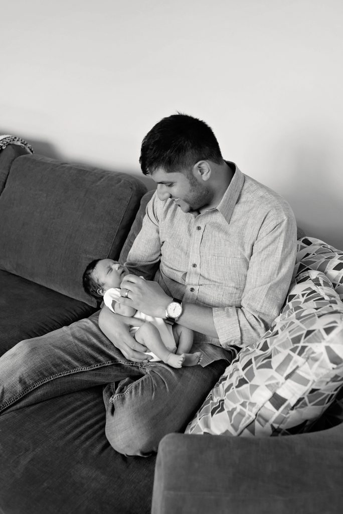 Father is holding his newborn son and smiling at him while being photographed by Talia Hannah Photography, Kitchener lifestyle newborn and family photographer