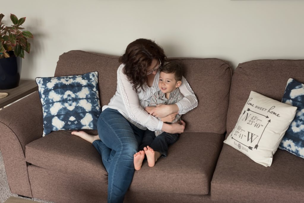 Mother is hugging her firstborn child during lifetsyle newborn photography session in Waterloo, Ontario