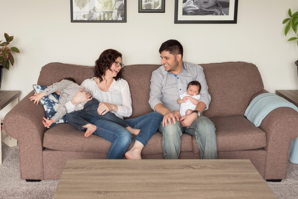 The family is sitting on the couch and smiling at each other during lifestyle newborn photography session in Kitchener